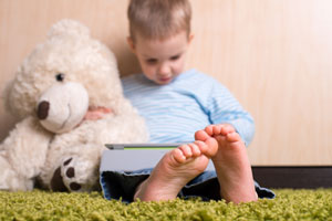 child with teddy bear and ipad